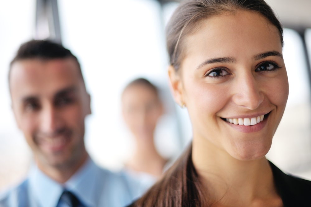 happy young business woman  with her staff,  people group in background at modern bright office indoors-1
